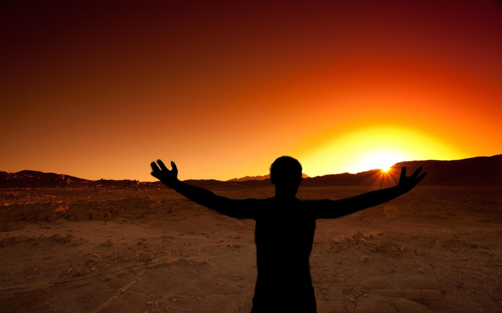 Man with out stretched hands toward the rising sun in the desert
